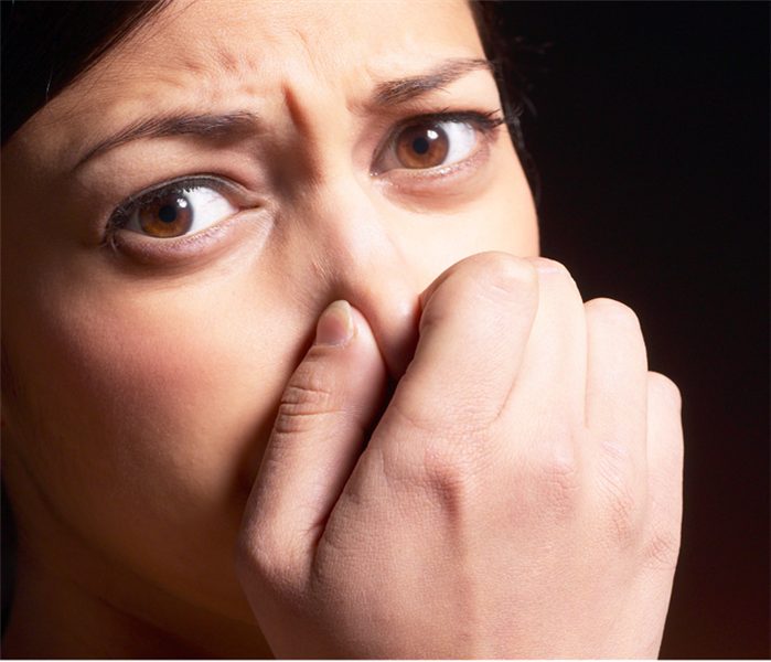 A brown Haired woman Smells something badly and using her nose to stop the scent. servpro can help
